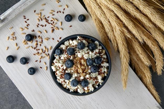 Mingau de aveia integral com sementes de linho, mirtilos, queijo cottage e espigas de trigo em uma bandeja de madeira pintada de branco