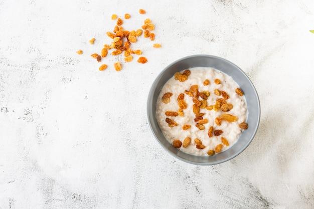 Mingau de aveia ou aveia de aveia ou cereais de café da manhã com as passas isoladas no fundo de mármore branco. comida caseira. saboroso café da manhã. foco seletivo. foto horizontal.