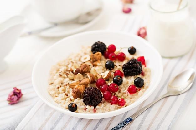 Mingau de aveia saboroso e saudável com frutas, sementes de linho e nozes. café da manhã saudável. comida de fitness.