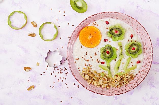Mingau de aveia saboroso e saudável com kiwi, romã e nozes. café da manhã saudável.