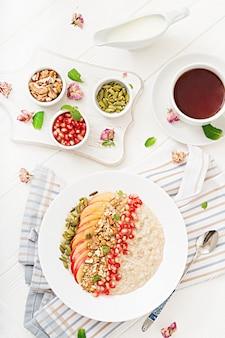 Mingau de aveia saboroso e saudável com maçãs, romã e nozes. café da manhã saudável. comida de fitness. nutrição apropriada. vista do topo.