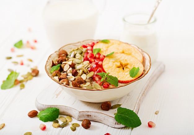 Mingau de aveia saboroso e saudável com maçãs, romã e nozes. café da manhã saudável. comida de fitness. nutrição apropriada