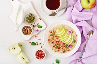 Mingau de aveia saboroso e saudável com maçãs, romã e nozes. Café da manhã saudável.