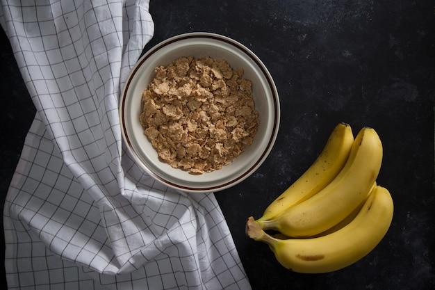 Mingau de aveia saudável orgânico com bananas frescas. a tigela de porcelana branca com guardanapo