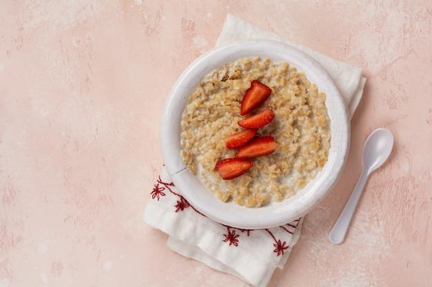 Mingau de aveia simples com morangos em um prato branco num guardanapo de linho no fundo rosa.