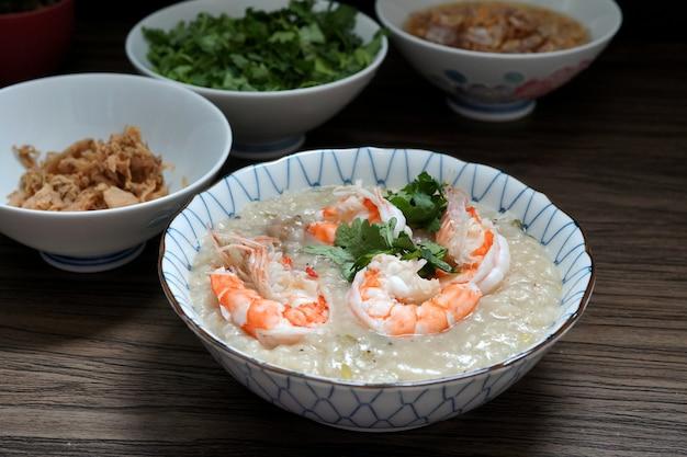 Mingau de camarão em uma tigela e picles de nabo, alho frito e óleo
