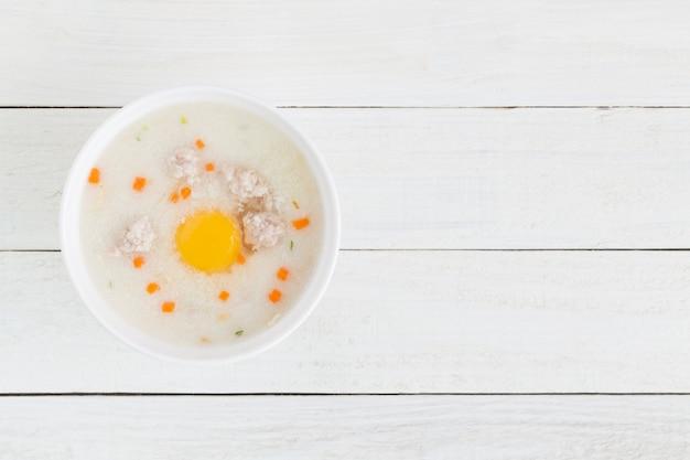 Mingau de carne de porco colocar ovos em um copo em um assoalho de madeira branco, vista superior e copie o espaço