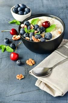 Mingau de cereais de aveia com frutas frescas na tigela preta. café da manhã saudável.