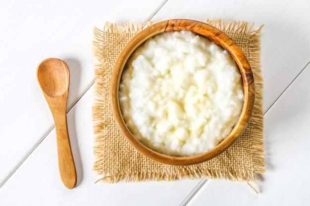 Mingau de leite de arroz com nozes e passas em taças de madeira sobre uma mesa de madeira branca