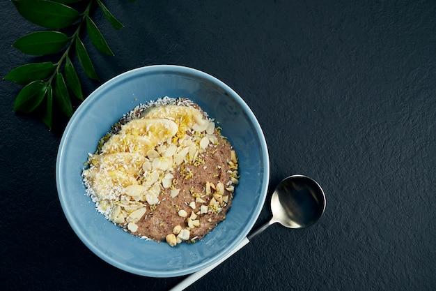 Mingau de linho com bananas, nozes, chocolate e coco em uma tigela azul sobre uma mesa preta. vista do topo. comida plana leigos. café da manhã saudável
