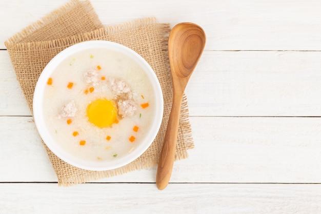Mingau de porco colocar ovos em um copo em um assoalho de madeira branco