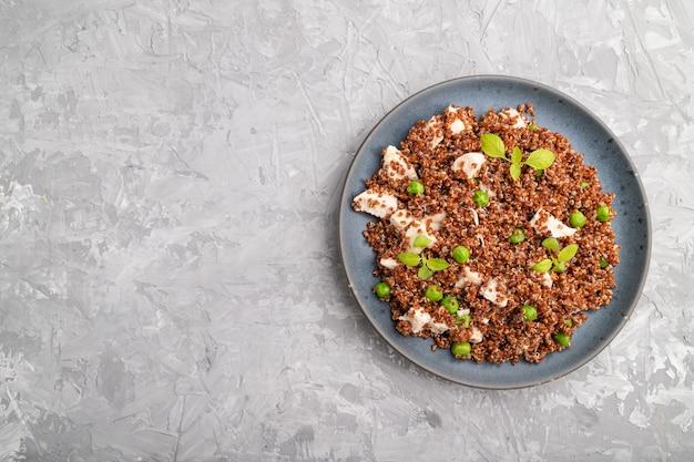 Mingau de quinoa com ervilha verde e frango na chapa de cerâmica sobre um fundo cinza de concreto.
