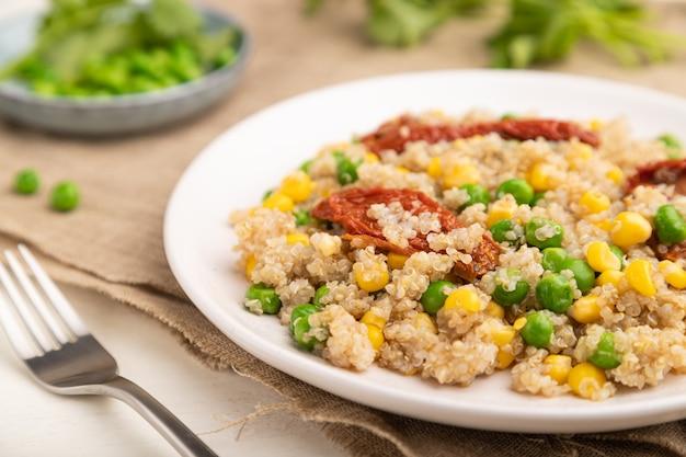 Mingau de quinua com ervilha, milho e tomates secos em um prato de cerâmica sobre uma superfície de madeira branca e tecido de linho