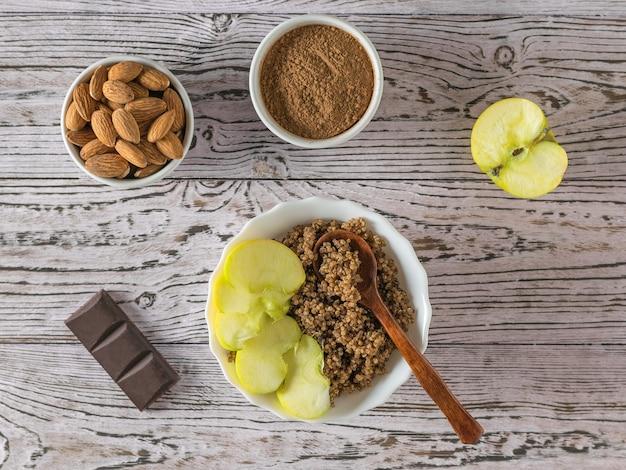Mingau de quinua com maçã e leite de amêndoa em uma mesa de madeira
