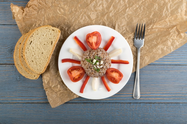Mingau de trigo mourisco de servir requintado na vista superior de fundo rústico de madeira. kasha russa ou trigo pseudocereal cozido decorado com tomate, cebola e verduras