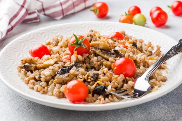 Mingau de trigo sarraceno com cogumelos e tomate cereja em um prato.
