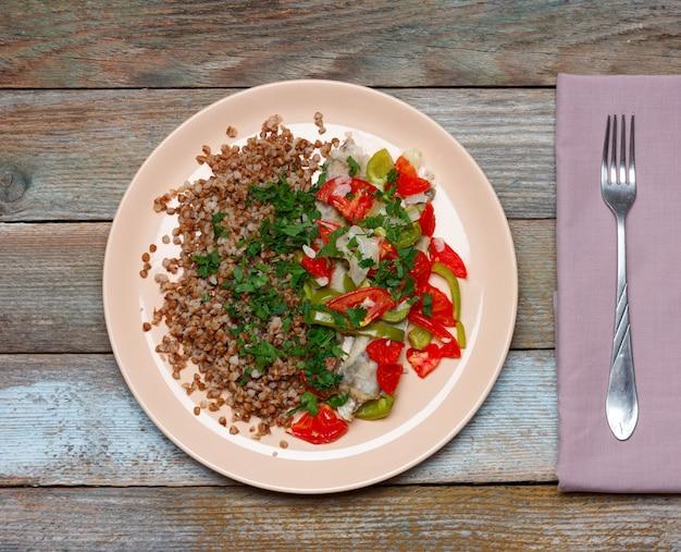 Mingau de trigo sarraceno com guarnição de peixe assado com legumes