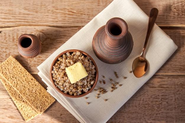 Mingau de trigo sarraceno com manteiga em uma tigela em branco de madeira