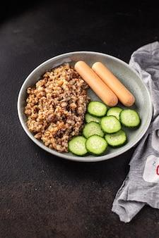 Mingau de trigo sarraceno e salsichas salada fresca pepino pronto para comer refeição lanche na mesa
