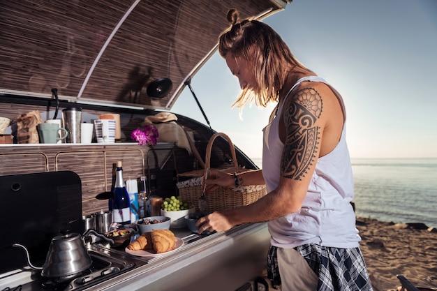 Mingau para mulher. homem loiro com tatuagem fazendo mingau matinal para sua mulher em uma casa móvel
