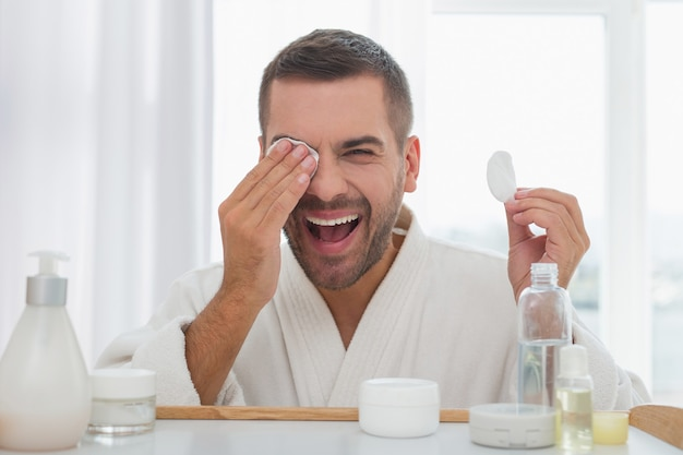 Minha beleza. homem alegre e positivo usando uma almofada de algodão em frente ao espelho