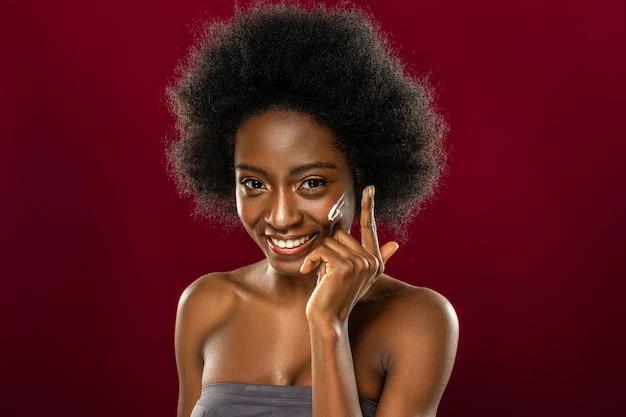Minha beleza. mulher simpática e positiva usando creme facial enquanto deseja ter uma pele perfeita