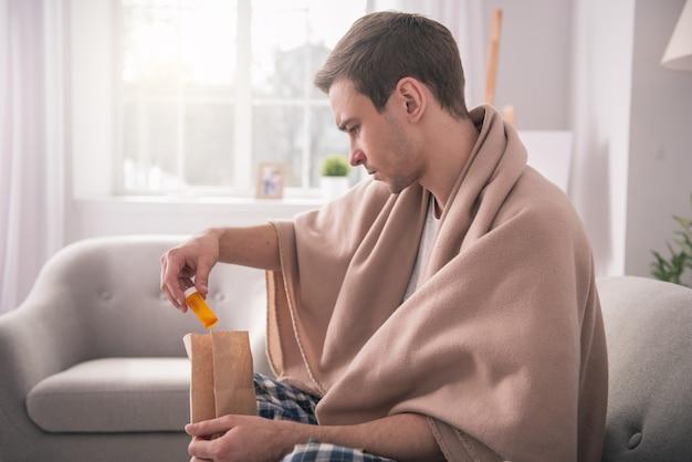 Minha entrega. jovem sério usando uma manta enquanto tira o remédio da sacola