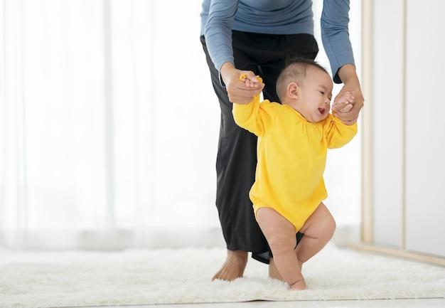 Minha garotinha dá os primeiros passos. família bebê feliz aprendendo a andar com a ajuda da mãe em casa