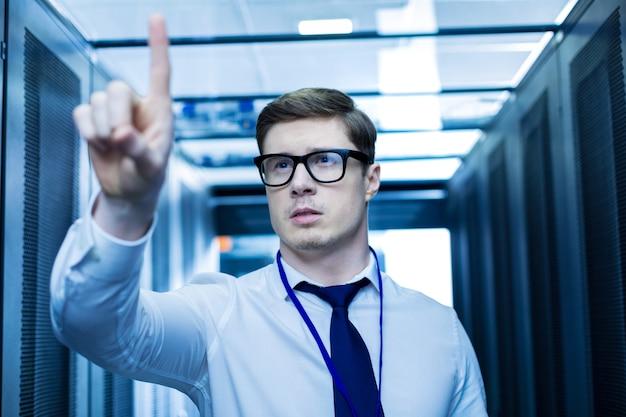 Minha imaginação. operador meditativo concentrado em pé perto dos gabinetes do servidor e apontando com o dedo