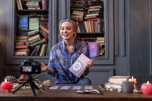 Minha impressão. mulher simpática e positiva falando sobre o livro enquanto compartilha suas impressões com os espectadores