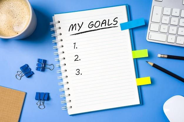 Minha lista em branco de metas no notebook com os equipamentos de escritório e uma xícara de café no fundo da mesa azul.