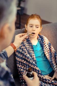 Minha medicação. linda garota pálida tomando a mistura para tosse enquanto está sentada no sofá