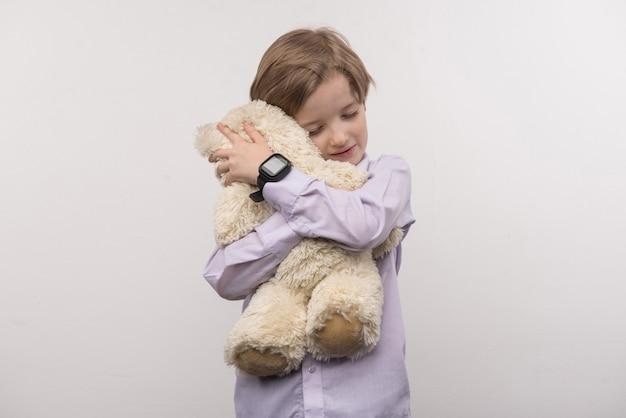 Minha melhor amiga. menino feliz e encantado abraçando seu brinquedo em pé contra um fundo branco
