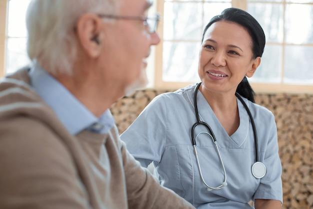 Minha paciente. atraente médico feliz vestindo uniforme enquanto olha para o homem sênior e sorrindo