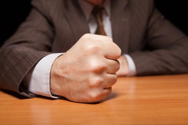 Minha palavra é lei! close-up de um homem em trajes formais, segurando o punho na mesa e isolado no preto