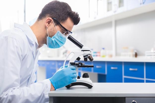 Minha pesquisa. moreno sério assistente de laboratório masculino posando em perfil enquanto olha no microscópio e estuda a amostra