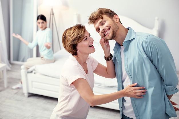 Minha querida mamãe. homem adulto alegre sorrindo enquanto está com sua mãe