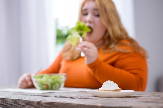 Minha sobremesa. mulher desolada e robusta olhando para a sobremesa e tomando café da manhã saudável