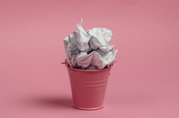 Mini balde com papel amassado em um fundo rosa.