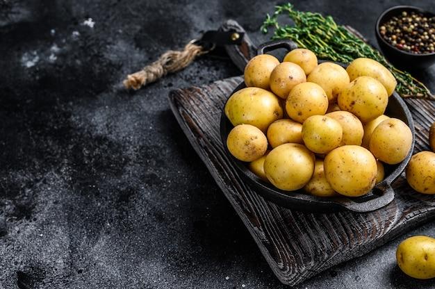 Mini batatas inteiras jovens em uma panela.