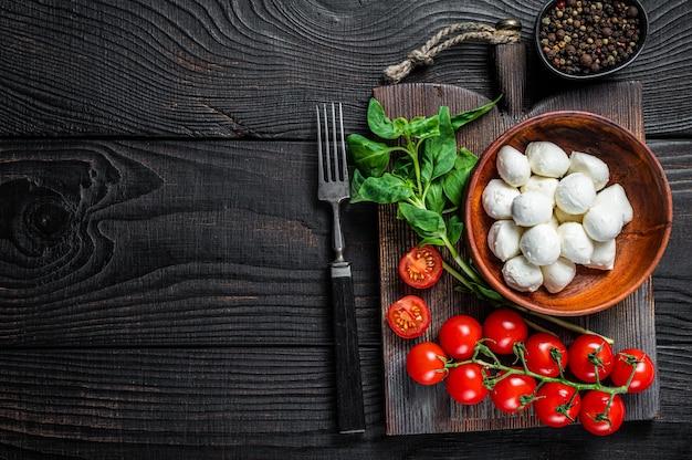 Mini bolinhas de queijo mussarela italiano, manjericão e tomate cereja pronto para cozinhar salada caprese. fundo de madeira preto. vista do topo. copie o espaço.