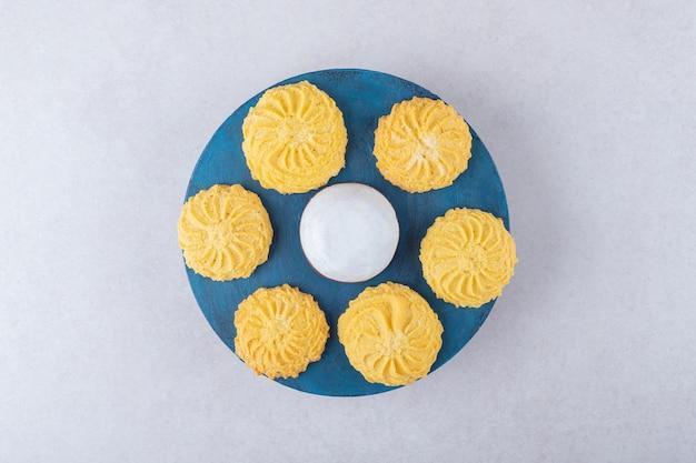 Mini bolo de mousse e deliciosos biscoitos num prato na mesa de mármore.