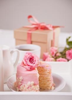 Mini bolo pequeno com esmalte rosa, lindas rosas, xícara de café, caixa de presente em cima da mesa branca.