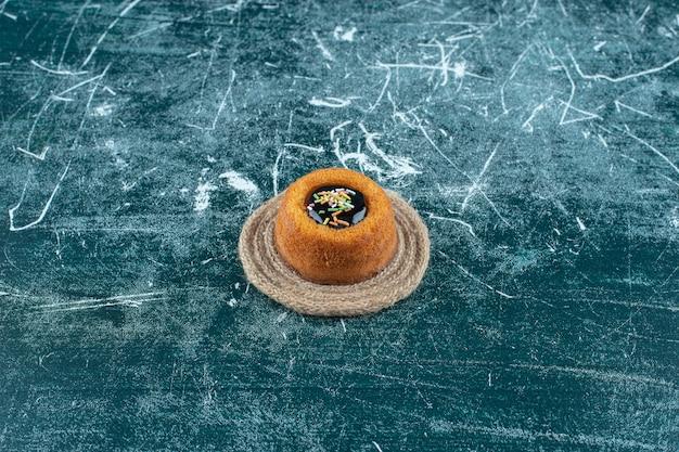 Mini bolo vitrificado em um tripé, sobre o fundo azul. foto de alta qualidade