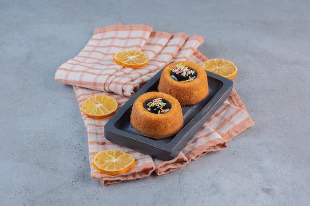 Mini bolos com geleia e rodelas de frutas na mesa de pedra.