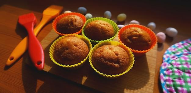 Mini bolos decorados com ovos, sobremesa de páscoa. mini muffins simples em assados coloridos de silicone. cozinha e conceito de cozinha em fundo de madeira