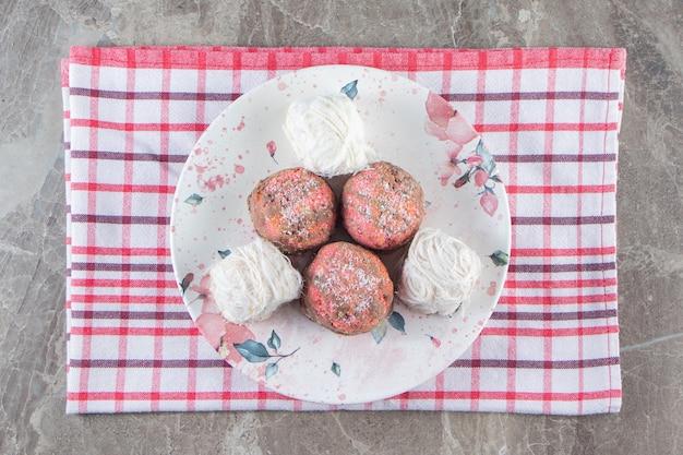 Mini bolos e algodão doce turco em um prato no pano de prato em azul.