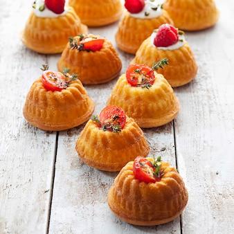 Mini bolos recheados com cream cheese e ricota guarnecidos com tomate e manjerona ou framboesa e pistache