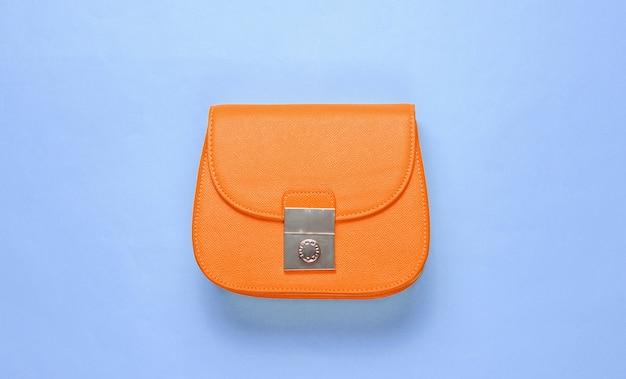 Mini bolsa de couro laranja sobre fundo azul. conceito de moda do minimalismo. vista do topo