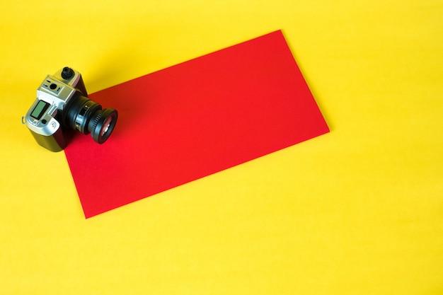 Mini câmera de brinquedo e envelope vermelho em fundo amarelo